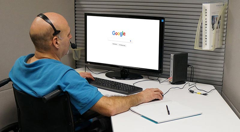 Disabled man sits at computer screen using screen reader software