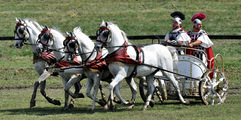 Four white horses before a white chariot carrying two men dressed in ancient garb