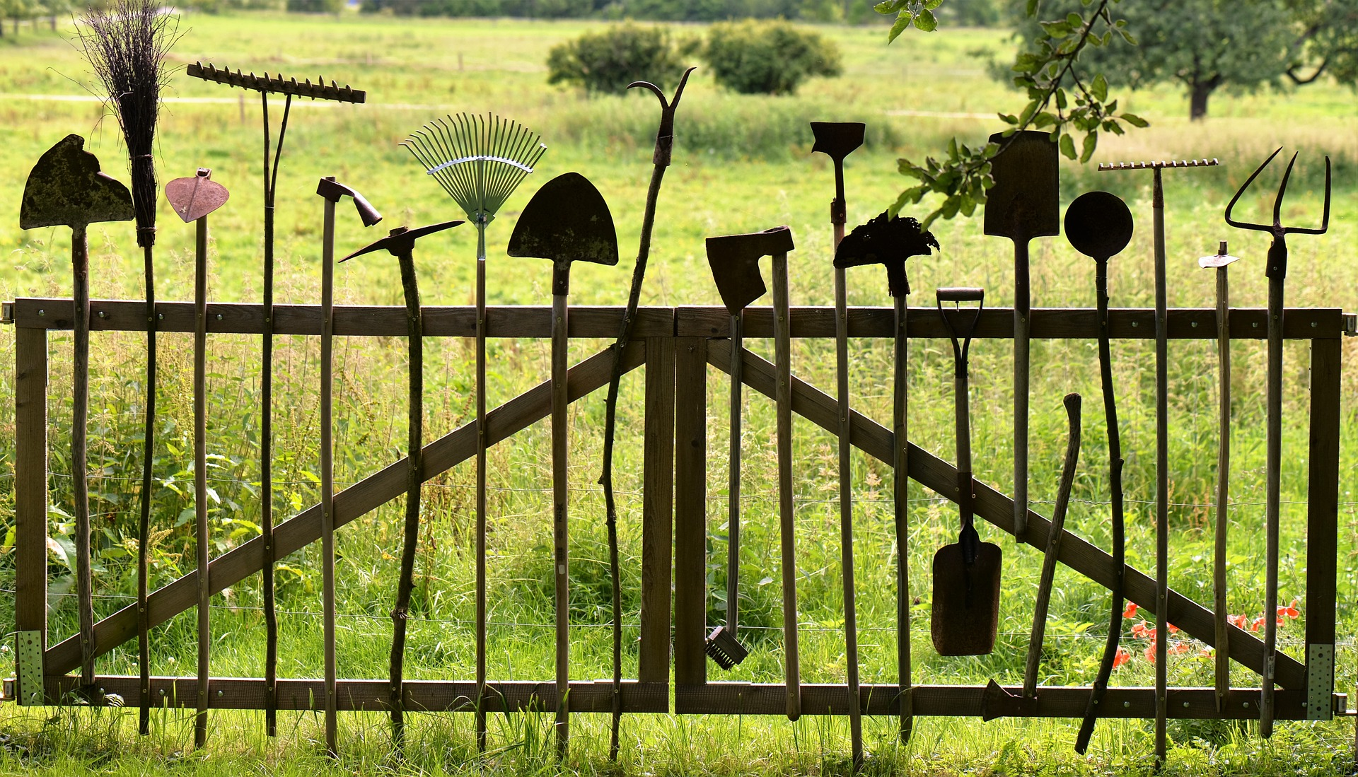 A row of various garden tools hanging from a fence